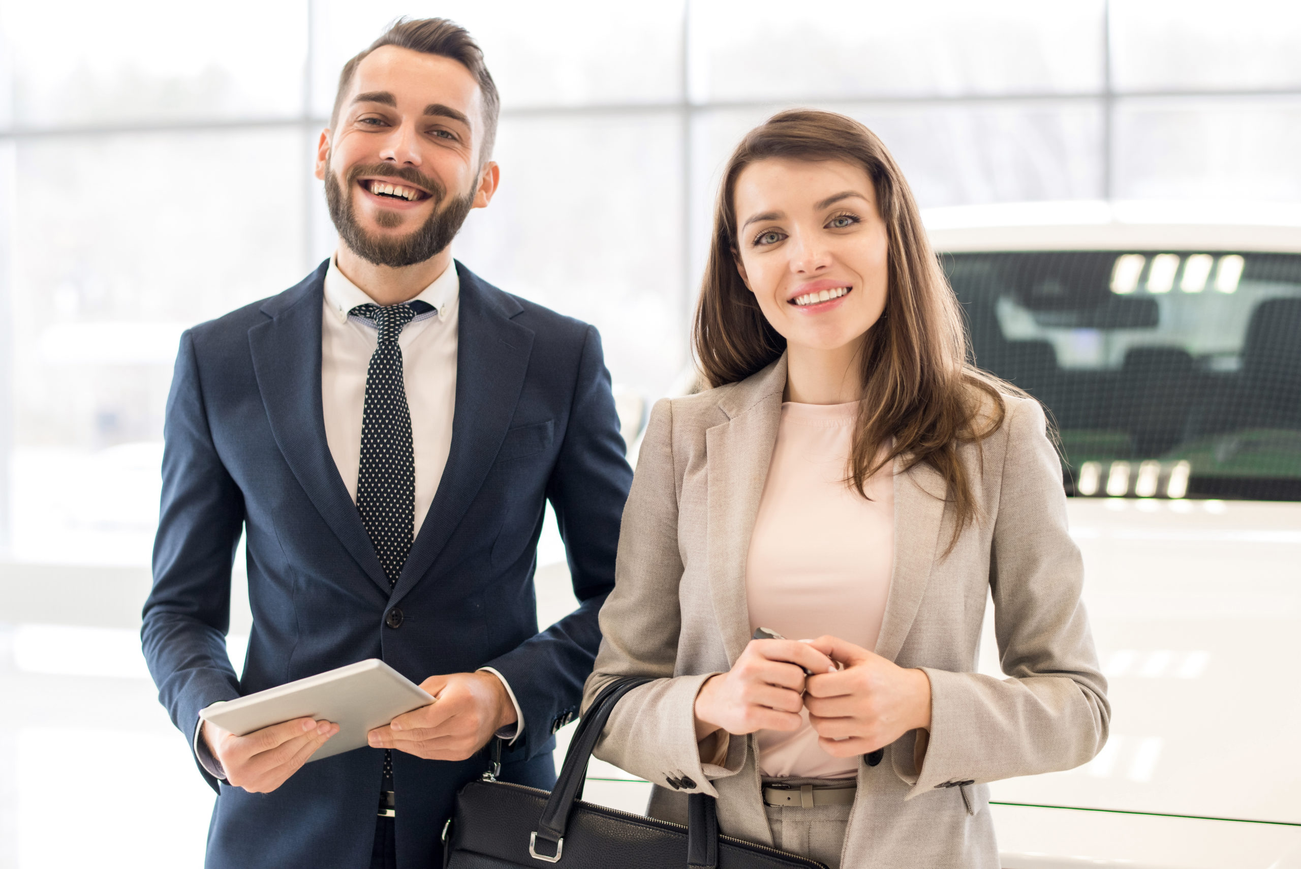 Portrait of beautiful business couple smiling cheerfully at camera coming to work in modern office building