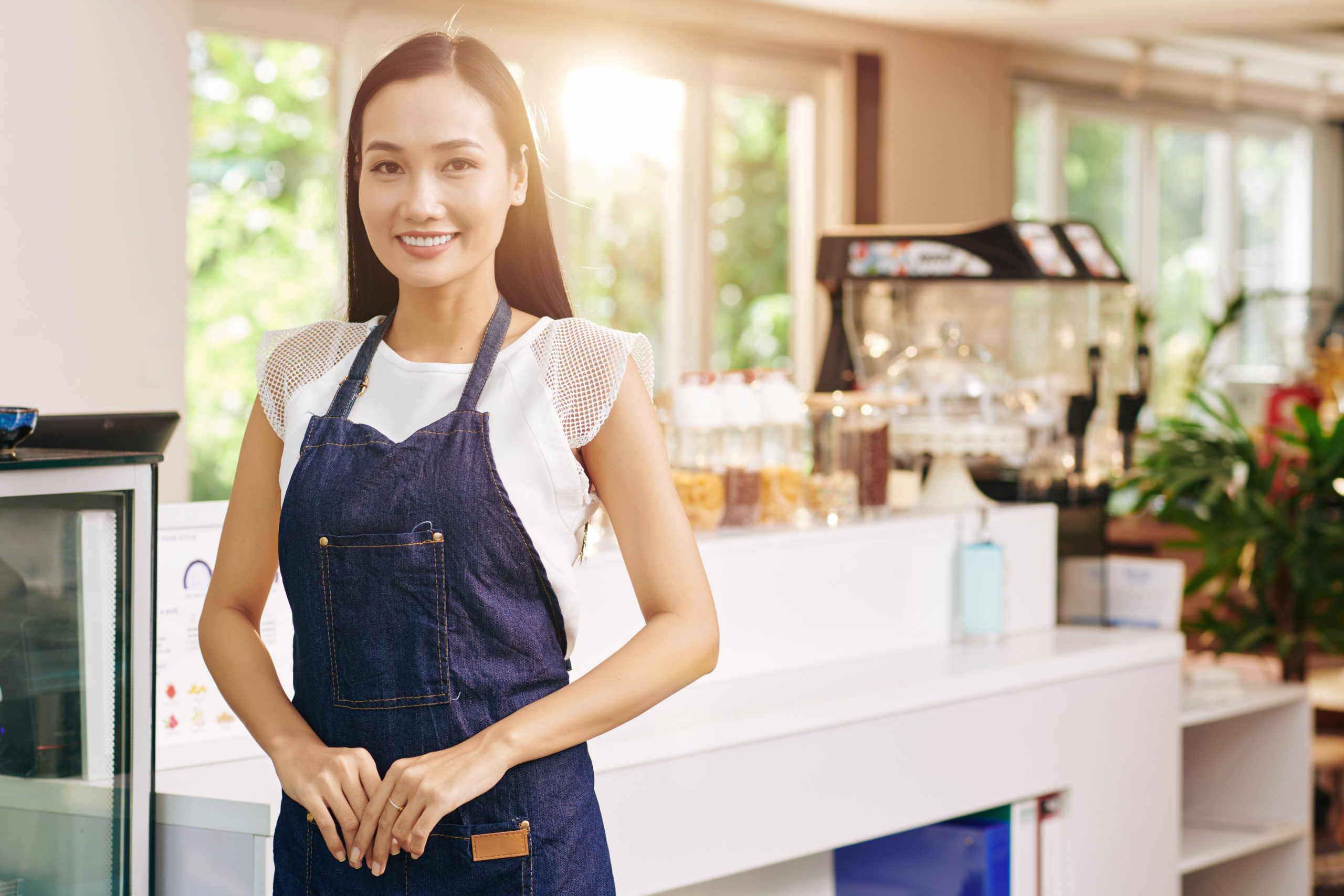 Happy successful young Vietnamese woman in denim apron standing in her coffeeshop or cafe